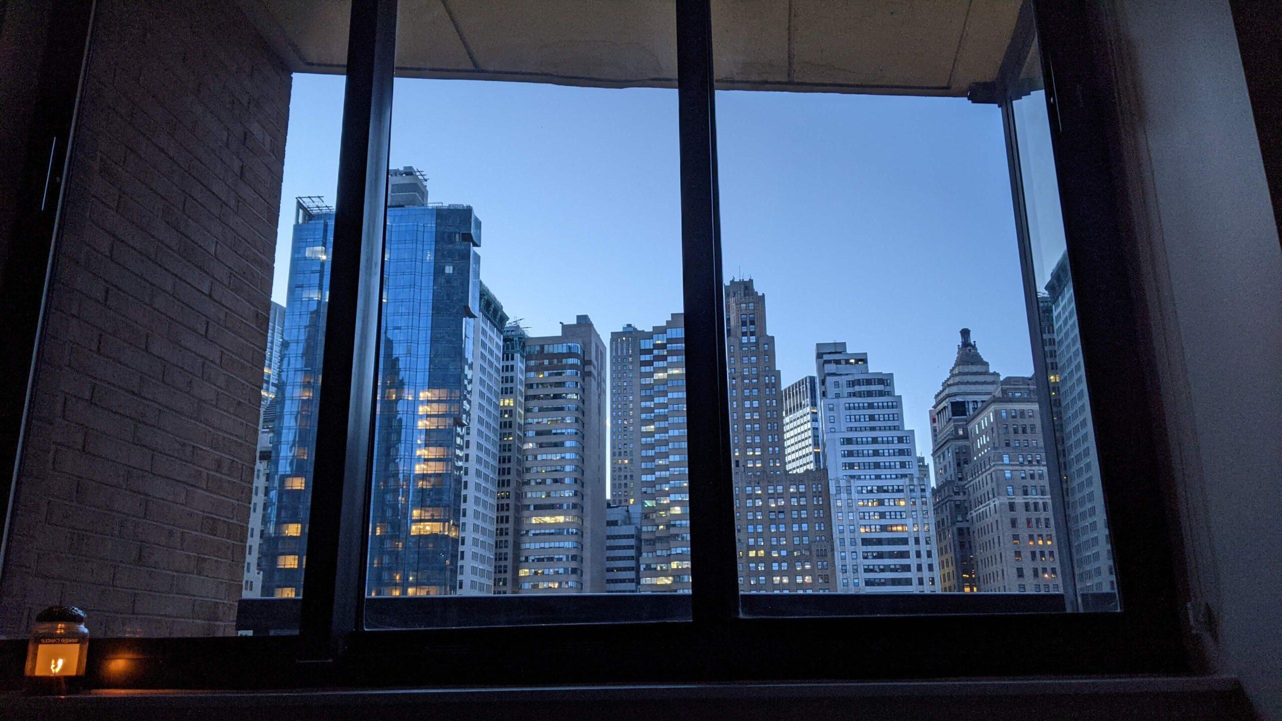 widok na nocny Manhattan z perspektywy łóżka z okna w sypialni