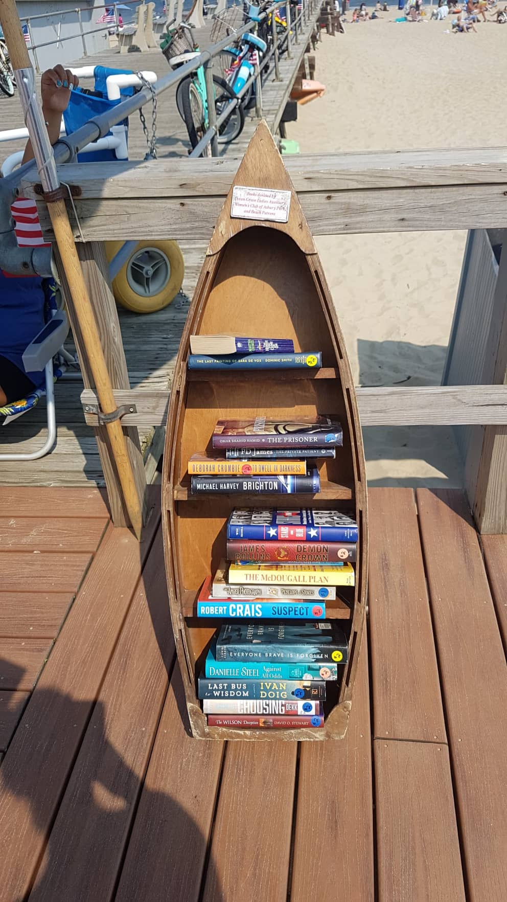 Mały regał w kształcie łódki zawierający książki do wypożyczenia przy plaży w Ocean Grove.