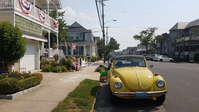 Śliczne uliczki w Ocean Grove - wiktoriańskie domki udekorowane amerykańskimi flagami i piękny żółty Volkswagen garbus.