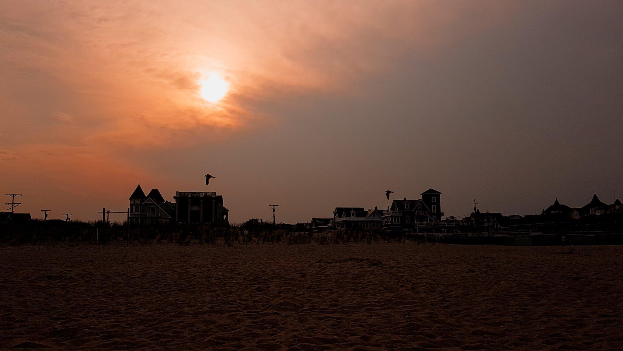 Zachodzące słońce nad plażowymi domkami w Ocean Grove, New Jersey.